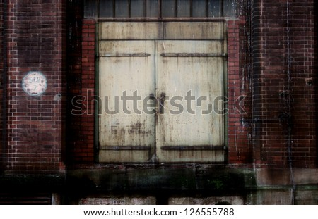 The photograph of an old steel door on a closed industrial area/Old steel door