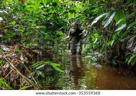The photographer in the jungle goes through a bog. Republic of Congo. Africa