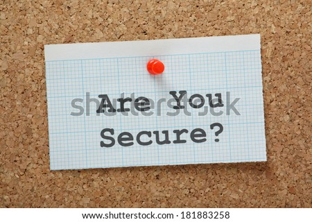 The phrase Are You Secure? typed on a piece of graph paper and pinned to a cork notice board - stock photo