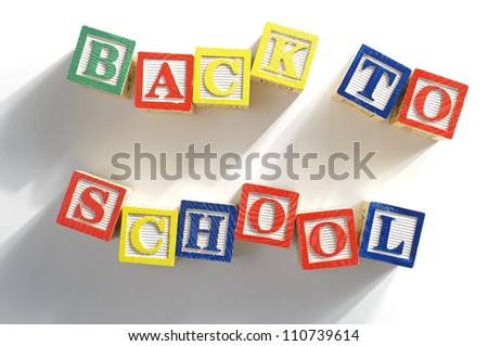 """The phrase """"BACK TO SCHOOL"""" spelled out in children's alphabet wood blocks. - stock photo"""