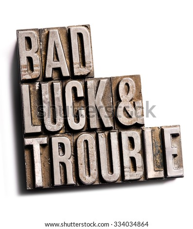 "The phrase ""Bad Luck & Trouble"" in letterpress type. Cross processed, narrow focus."