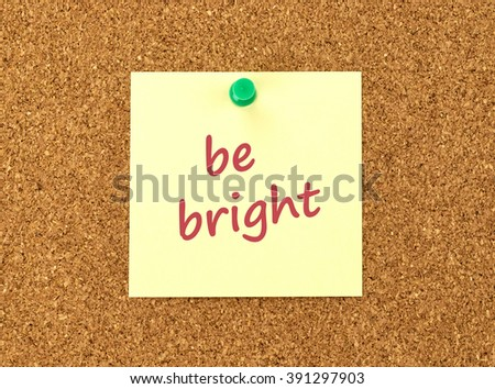 The phrase Be Bright in red text on a yellow sticky note posted to a cork notice board.