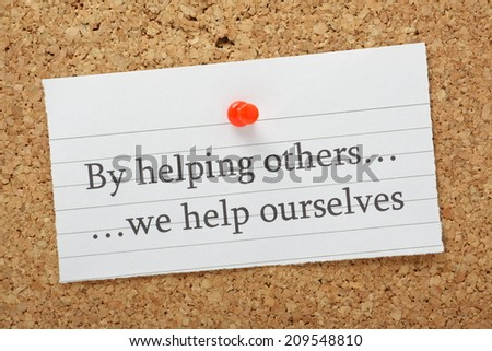 The phrase By helping others we help ourselves typed on a piece of lined paper pinned to a cork notice board - stock photo