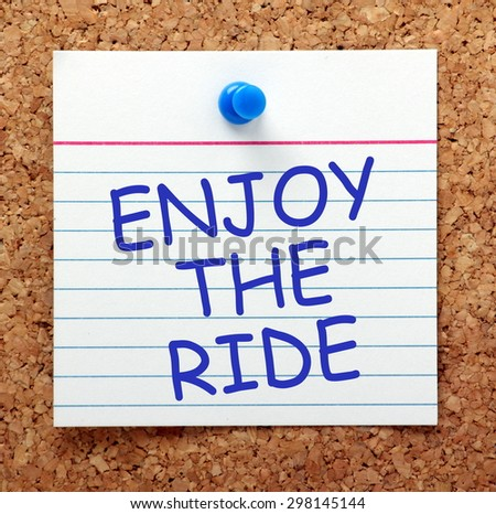 The phrase Enjoy The Ride in blue text on an index card pinned to a cork notice board as a reminder - stock photo