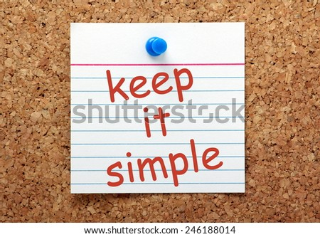 The phrase Keep It Simple in red ink on a white index card pinned to a cork notice board as a reminder - stock photo
