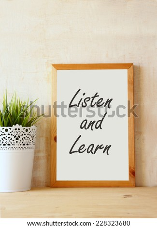 the phrase listen and learn written over white drawing board against rustic textured wall - stock photo