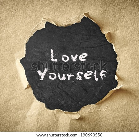 the phrase love yourself written over chalkboard through torn paper - stock photo