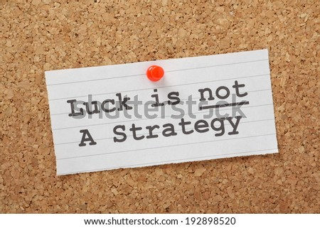 The phrase Luck is not a Strategy on a cork notice board as a reminder that your business or life plans cannot succeed on good fortune alone - stock photo