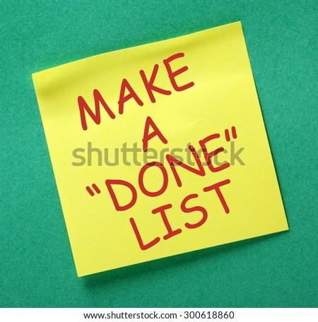 The phrase Make A Done List in red text on a yellow sticky note posted on a green notice board as a source of motivation - stock photo