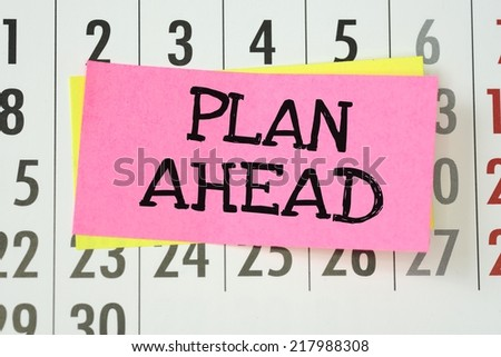 The phrase Plan Ahead written on sticky paper note and stuck on a wall calendar background - stock photo