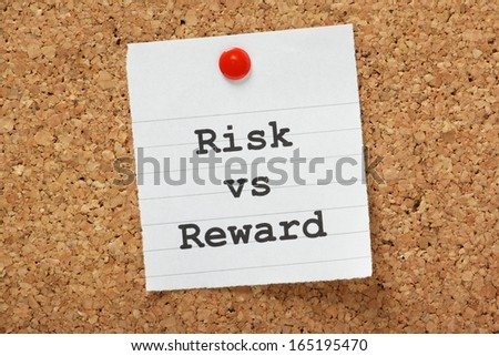 The phrase Risk vs. Reward typed onto a piece of lined paper and pinned to a cork notice board. - stock photo