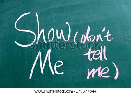 The phrase Show Me, Don't Tell Me written by hand in white chalk on a used blackboard. Often used in business but more so as a guide for novel and book writers - stock photo