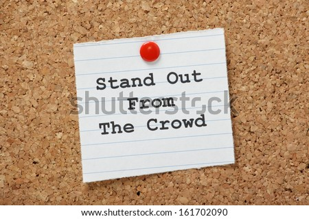 The phrase Stand Out From The Crowd on a paper note pinned to a cork notice board. It is important to demonstrate the differences or unique skills we can bring to a new job or relationship. - stock photo