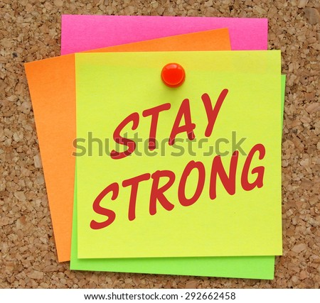 The phrase Stay Strong in red text on a yellow sticky note pinned to a cork notice board - stock photo