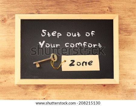 the phrase step out of your comfort zone written on blackboard  - stock photo