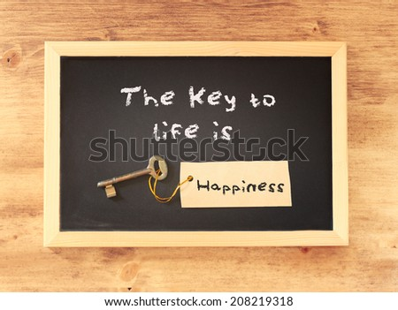the phrase the key to life is happiness written on blackboard - stock photo