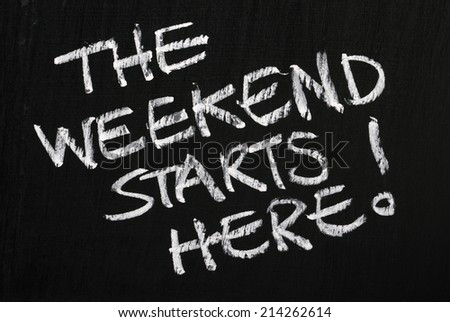 The phrase The Weekend Starts Here! written in white chalk on a used blackboard - stock photo