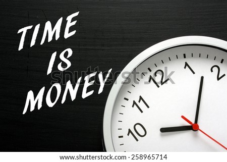 The phrase Time Is Money written on a blackboard next to a modern wall clock - stock photo
