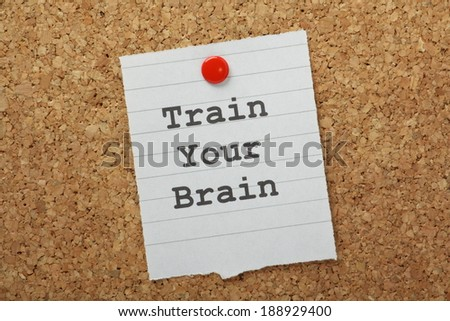 The phrase Train Your Brain typed on a piece of paper and pinned to a cork notice board - stock photo