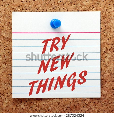 The phrase Try New Things in Red text on an index card pinned to a cork notice board as a reminder - stock photo
