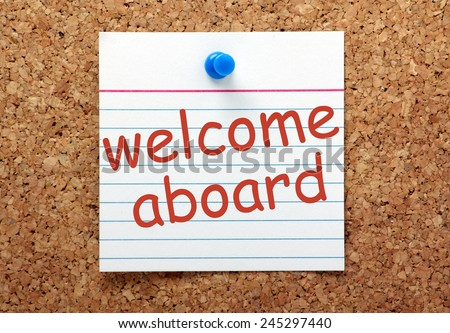 The phrase Welcome Aboard printed on a lined index card and pinned to a cork notice board - stock photo