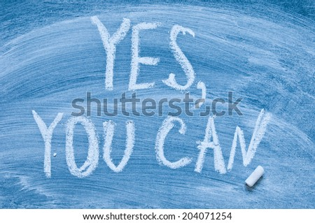 The phrase Yes You Can written by hand on a blackboard - stock photo