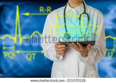 the physician obtains a description of the electrocardiogram on the tablet as a hologram - stock photo