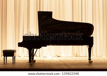 The piano on the brown curtain background - stock photo