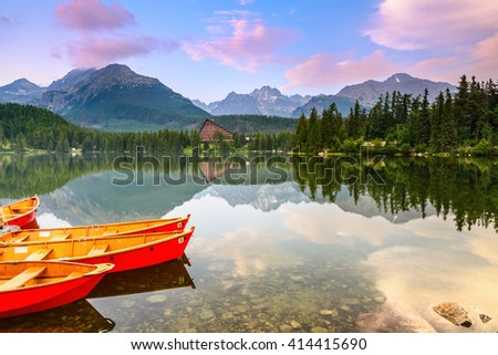 The picture captures the view of a person watching boats reverie, calm lake, fantastic mountains and the clouds floating across the sky - stock photo