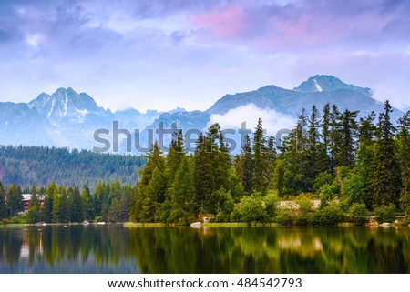 The picture captures the view of a person watching  calm lake, fantastic mountains and the clouds floating across the sky