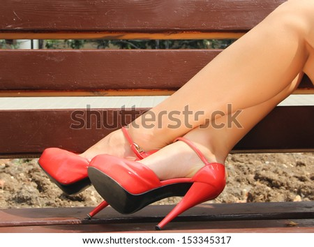 The picture shows a beautiful female legs in elegant, red shoes.