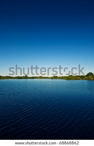 The picture shows a lake and a blue sky. - stock photo