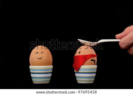 The picture shows an egg which is attacked by another one. - stock photo