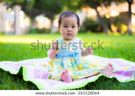 The picture shows . Nature light with grass background  Happy child playing on green grass outdoors in spring park,baby playing With the soccer ball ,asian baby playing at the park - stock photo