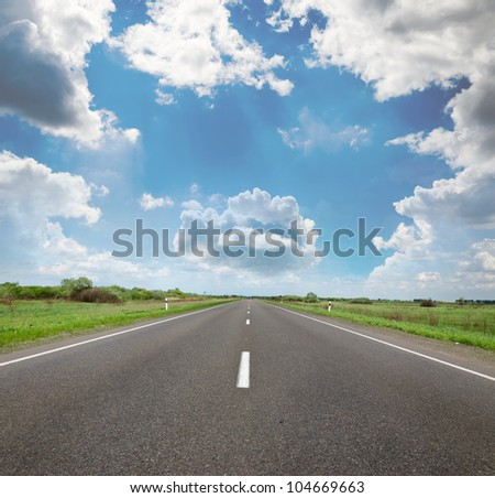 The picturesque country road in the background of the relief of the sky.