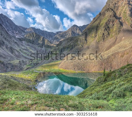 The picturesque lake in a small valley below the mountain peak. Eastern Sayan. The Republic Of Buryatia - stock photo