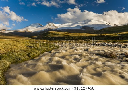 The picturesque landscape with mountains and stream on a background of white clouds.