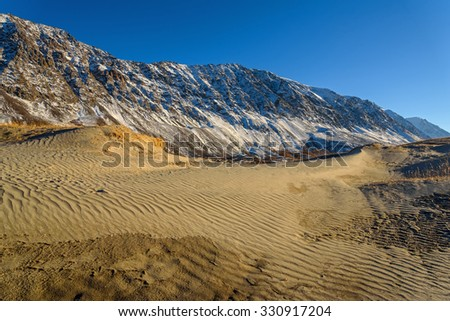 The picturesque mountain autumn landscape with snow covered mountains, frozen lake, sand dunes with sparse vegetation against the blue sky on a sunny day