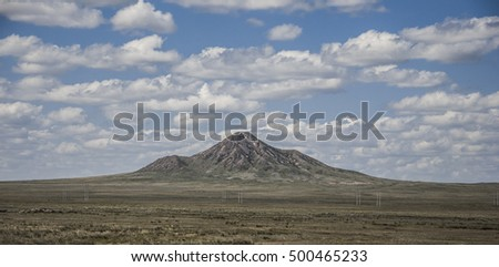 The picturesque steppe landscape with mountain, steppes with sparse vegetation on a background of blue sky with clouds