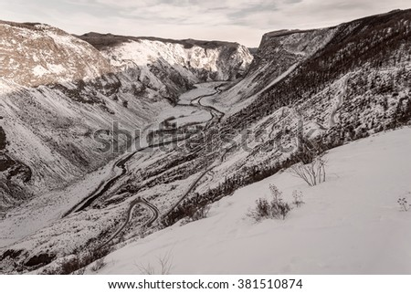 The picturesque top view on the mountains covered with snow, the valley between the mountains and a steep winding road in the form of serpentine the leading down to the valley in winter - stock photo