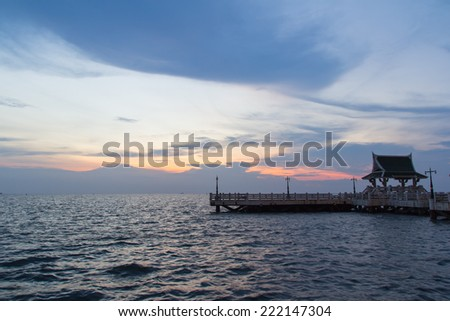 The pier at sunset blurs the sea and bathes the structure in the warm glow of the sun  in Thailand - stock photo