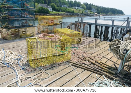 The pier of a working harbor strewn with equipment as New England Lobstermen prepare for another outing - stock photo