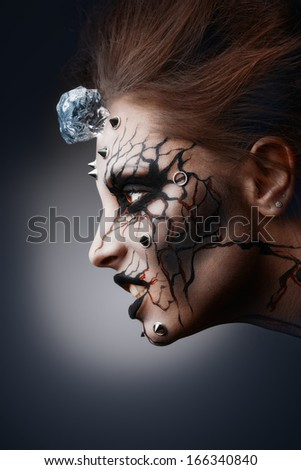 The pierced female face painted as a grinning halloween witch with a cracked paint and an ice cube. - stock photo
