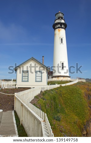 The Pigeon Point Lighthouse and white picket fence located in Pigeon Point Light Station State Historic Park between Half Moon Bay and Santa Cruz on the central California coast - stock photo