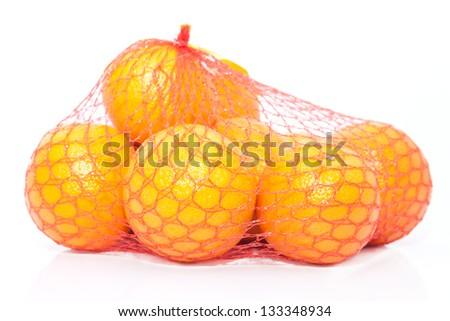The pile of fresh oranges in the string bag