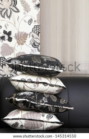 the pillows put at each other on a sofa opposite to a curtain - stock photo