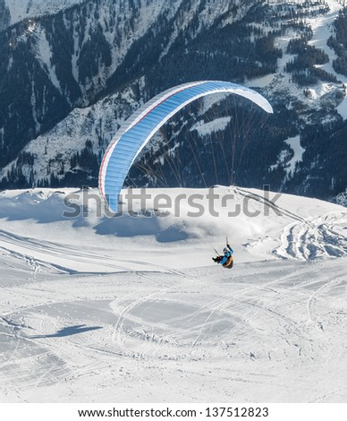 The pilot flies a paraglider with a mountain-skiing slope of Penken - Mayrhofen, Austria