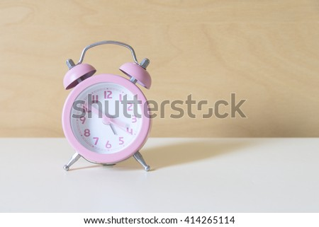 the pink analog alarm clock with the wooden background - stock photo