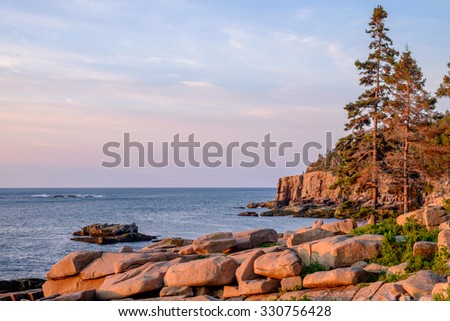 The pink granite slabs of granite along the Maine coast glow in the new morning sunrise light - stock photo