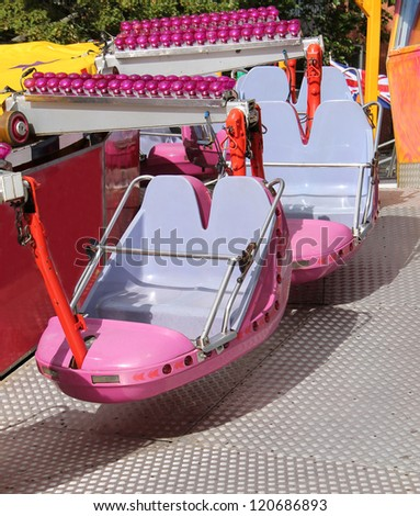 The Pink Riding Cars of a Fast Fun Fair Ride.
